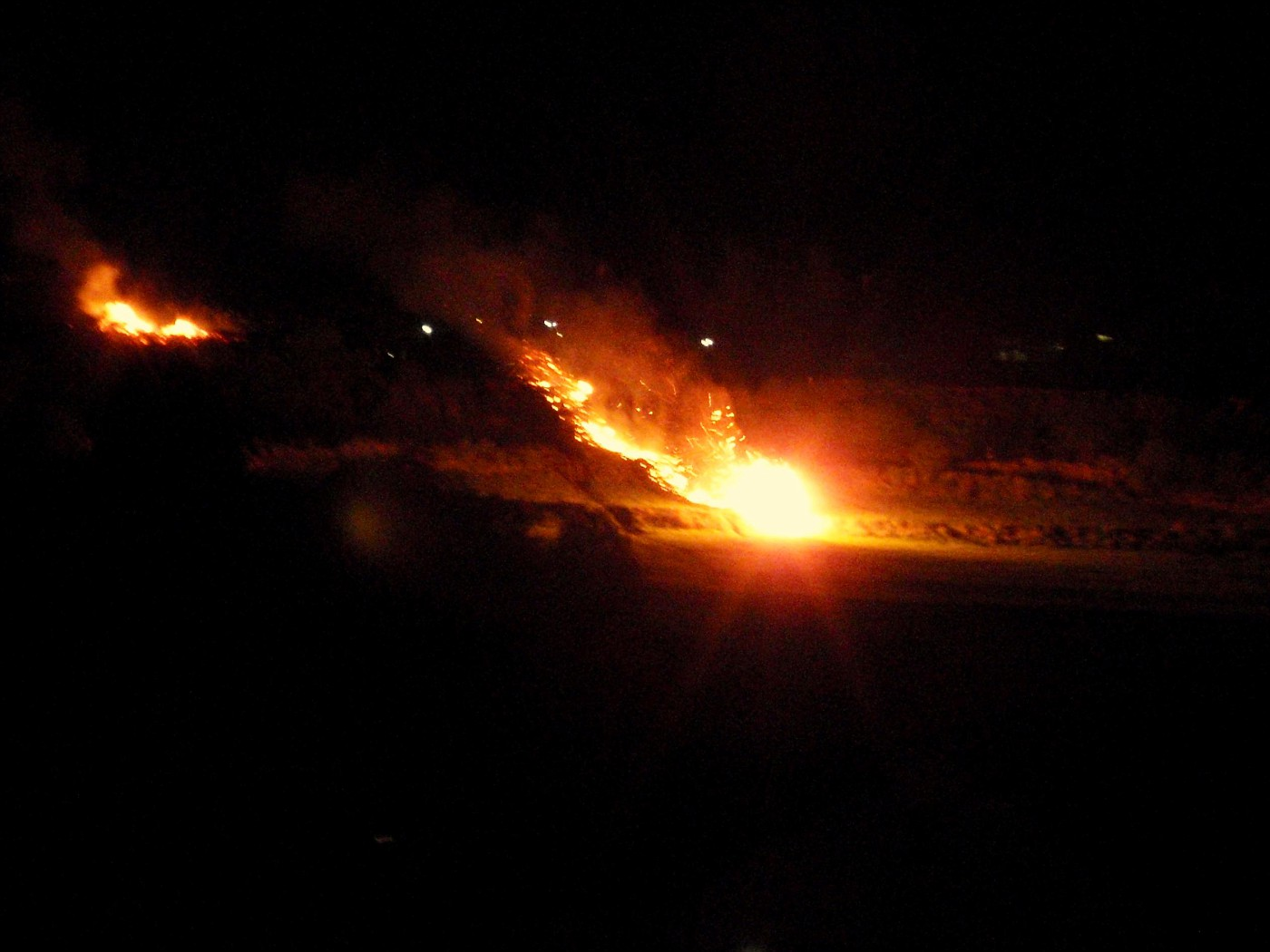 Ein flammend brennendes Osterrad rollt den Berg hinab