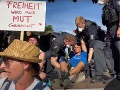 Auch der Rechtsanwalt Markus Haintz wird durch die Polizei von der Bühne getragen.